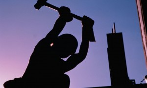 Construction worker using sledgehammer, silhouette